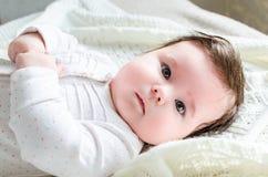 Bebé recién nacido lindo en el traje del mameluco que miente en la manta de lana Fotos de archivo