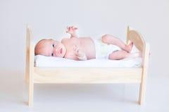 Bebé recién nacido lindo en una cama del juguete Foto de archivo libre de regalías