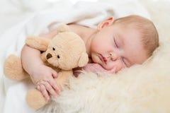 Bebé con el juguete que duerme en cama de la piel Foto de archivo libre de regalías