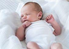 Bebé recién nacido que duerme en el suyo detrás fotografía de archivo