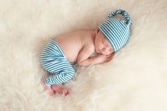 Pijamas que llevan del bebé recién nacido el dormir foto de archivo