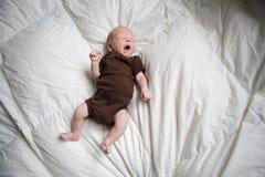 Bebé recién nacido que duerme en su cama. Fotos de archivo
