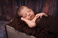 Bebé recién nacido que duerme en un cajón rústico Fotografía de archivo