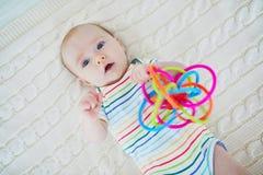 Bebé recién nacido que juega con el juguete colorido Fotos de archivo libres de regalías