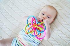 Bebé recién nacido que juega con el juguete colorido Fotografía de archivo