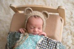 Bebé recién nacido que lleva un capo del oso imagenes de archivo