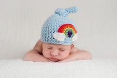 Bebé recién nacido que lleva un sombrero del arco iris Fotografía de archivo