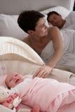 Bebé recién nacido que llora en choza en dormitorio de los padres fotografía de archivo