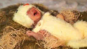 Bebé recién nacido que llora en traje del pollo en cama de la piel metrajes