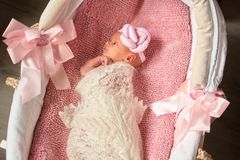 Bebé recién nacido que miente comfortablemente en cesta del bebé fotos de archivo