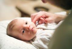 Bebé recién nacido que miente en cama, padre irreconocible que frota ligeramente su cabeza imagenes de archivo