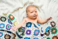 Bebé recién nacido que miente en la cama, cubierta por una manta hecha a ganchillo Visión superior foto de archivo