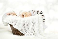Bebé recién nacido que miente en la cesta, sombrero hecho punto de lana del niño recién nacido foto de archivo