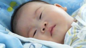 Bebé recién nacido que miente y que se relaja en la cama Concepto sano de los niños metrajes