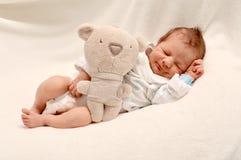 Bebé recién nacido sonriente que duerme con el oso de peluche fotografía de archivo libre de regalías
