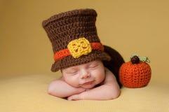 Bebé recién nacido sonriente que lleva un sombrero del peregrino