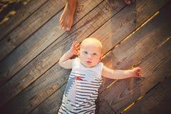Bebé recién nacido una mentira rubia en su parte posterior en un muelle de madera del fondo, embarcadero del año en la opinión ra Foto de archivo