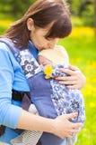 Bebé recién nacido y madre al aire libre que caminan con la honda imagen de archivo libre de regalías