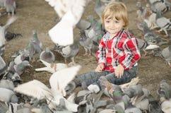 Bebé rodeado por Doves Fotografía de archivo