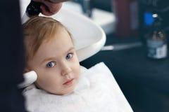 Bebé rubio lindo asustado serio y pequeño con los ojos azules en una peluquería de caballeros que tiene cabeza que se lava del pe imagenes de archivo