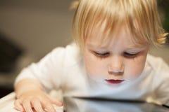 Bebé rubio que mira la tableta de la pantalla Imagenes de archivo