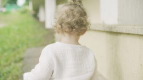 Bebé rubio rizado que camina, tiro del primer de la parte posterior almacen de video