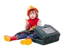 Bebé serio en el casco de protección con las herramientas Foto de archivo libre de regalías