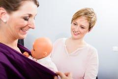 Bebé simulado que lleva de la mujer en honda fotos de archivo