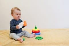 Bebé smilling y que juega con los juguetes coloridos en casa fondo del niño con el espacio de la copia Desarrollo temprano para l imagenes de archivo