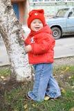 Bebé sonriente cerca del árbol Fotografía de archivo
