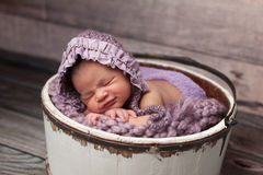 Bebé sonriente con el capo de la lila que duerme en un cubo foto de archivo libre de regalías