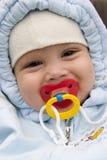 Bebé sonriente con el pacificador Fotografía de archivo libre de regalías