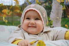 Bebé sonriente con las hojas de otoño Foto de archivo libre de regalías