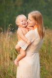 Bebé sonriente de los asimientos de la madre   Imagen de archivo
