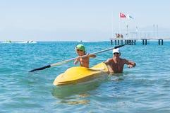 Bebé sonriente del abuelo y del nieto pequeño en gorra de béisbol verde kayaking en el mar tropical del océano en el tiempo del d Fotos de archivo