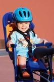Bebé sonriente en asiento de bicicleta Foto de archivo