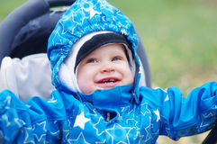 Bebé sonriente en el carro de bebé al aire libre Imagen de archivo