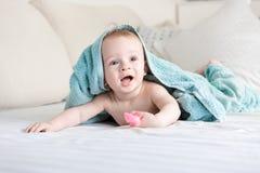 Bebé sonriente feliz debajo de la toalla azul que se arrastra en cama con s blanco Imagenes de archivo