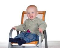 Bebé sonriente feliz en un highchair Imagenes de archivo