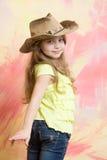 Bebé sonriente feliz que lleva un equipo de la muchacha de la vaca con el sombrero Foto de archivo