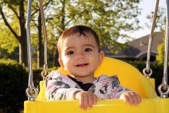 Bebé sonriente lindo en el oscilación del compartimiento Foto de archivo libre de regalías