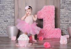 Bebé sonriente lindo en vestido rosado Imagenes de archivo
