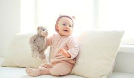 Bebé sonriente lindo feliz con el hogar del juguete del oso de peluche en el sitio blanco Foto de archivo libre de regalías