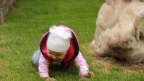 Bebé sonriente lindo que se arrastra en una hierba verde en el parque de la ciudad metrajes