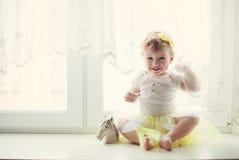 Bebé sonriente que se sienta cerca de la ventana Foto de archivo libre de regalías