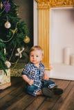 Bebé sonriente que se sienta debajo del árbol de Chritmas cerca de la chimenea Imágenes de archivo libres de regalías
