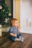 Bebé sonriente que se sienta debajo del árbol de Chritmas cerca de la chimenea Imagen de archivo libre de regalías