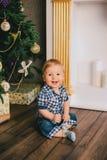 Bebé sonriente que se sienta debajo del árbol de Chritmas cerca de la chimenea Foto de archivo
