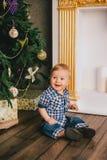 Bebé sonriente que se sienta debajo del árbol de Chritmas cerca de la chimenea Fotos de archivo