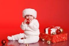 Bebé sonriente que se sienta en piso con la decoración de la Navidad Fotografía de archivo